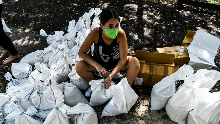 A woman prepares sand bags for distribution to the residents of Palmetto Bay near Miami