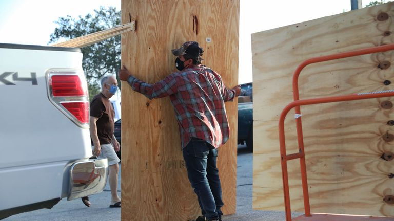 A man is seen loading plywood onto his truck so he can board up his home before the storm's arrival