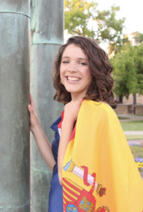 Girl smiling and holding flag of Spain